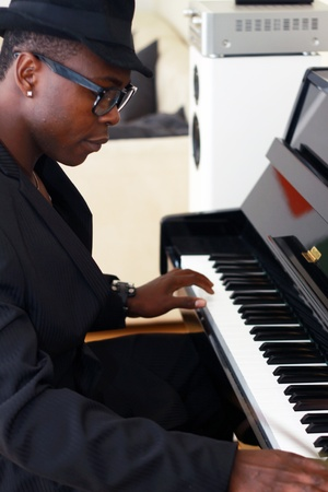 young musician: Black musician plays the piano - photographed from the side