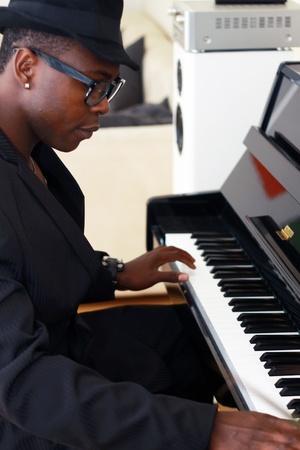 m�sico: M�sico negro toca el piano - fotografiada desde el lado Foto de archivo