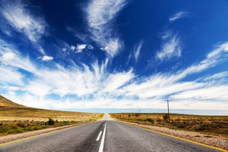 get away: Endless, lonely road or highway, which runs towards the horizon. Stock Photo