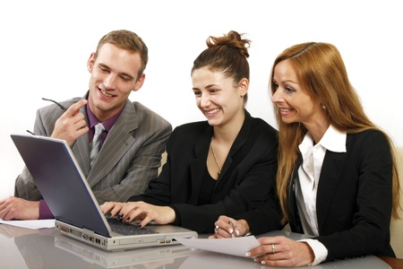 happier: Friendly team working in the office. Two women and a man sitting in front of a computer and smiling. Horizontal format and text space
