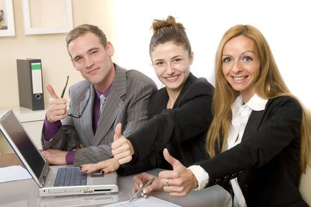 Positive team in the office shows up the thumb. Two women and a man sitting in front of a computer and smiling. Horizontal format and text space
