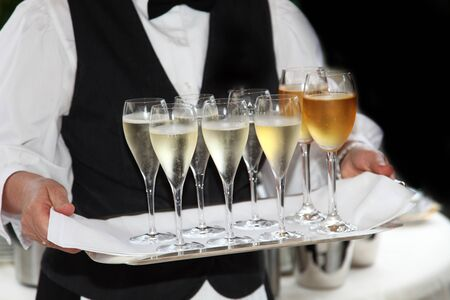 Waiters served champagne and wine - in the foreground are the champagne - and wine glasses on a tray to see. photo