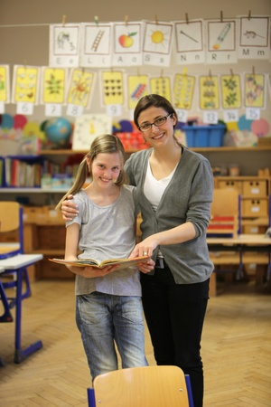 schooltime: smiling student and teacher in the classroom - hochformat