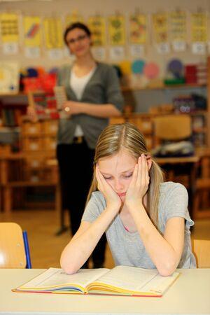 educators: estresado estudiante de la escuela con un libro delante de. En el fondo es el maestro.