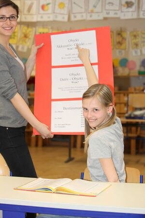 industrious: German teacher and pupil hours in the classroom to learn together and smiling  Stock Photo