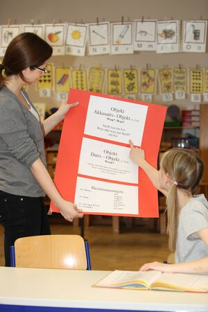 German lessons in primary school - teacher and student together to practice photo