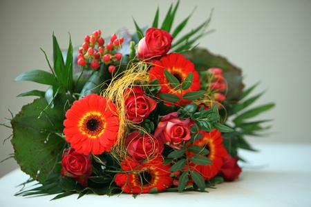 Colourful floral bouquet of orangey-red flowers in green foliage lying on a tabletop  photo