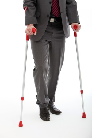 hobble: Lower body of a disabled or injured businessman walking on a pair of crutches, studio on white