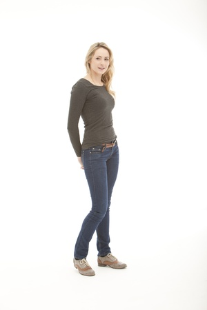 svelte: blonde woman wearing a long sleeve shirt with her hands on her back pocket standing on a white seamless background Stock Photo
