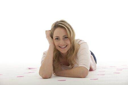 lying down: blonde woman wearing a light pink blouse lying on her stomach Stock Photo