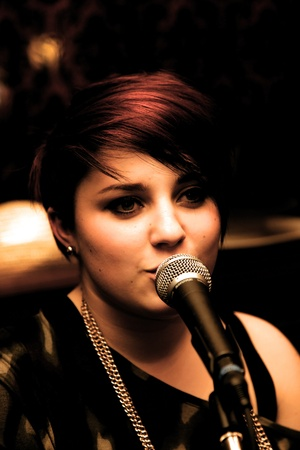 Urban girl with short hair sings on microphone