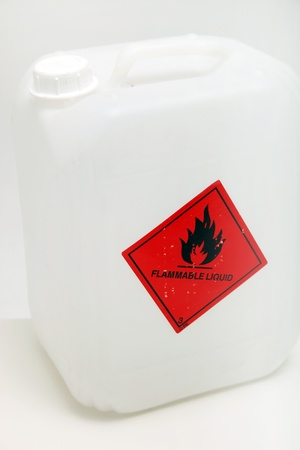 White plastic container with a red flammable hazard label on the outside