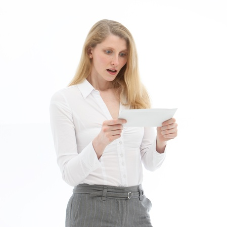 dismay: Attractive blonde businesswoman reacting in shock and disbelief on reading bad news