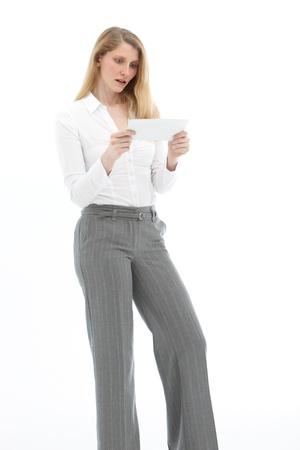 sgomento: Piuttosto giovane donna bionda reagire con sgomento e incredulit� durante la lettura di una lettera contenente una cattiva notizia