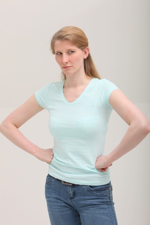 irked: Studio shot of envious blonde woman on gray background