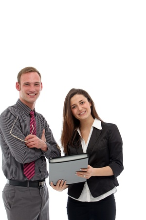 folio: Young attractive smiling businessman and businesswoman standing looking at a folio together during an informal meeting and discussion isolated on white Stock Photo
