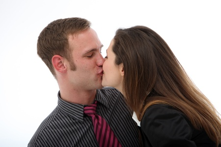 spontaneous: Young affectionate couple in business attire enjoying a spontaneous kiss isolated on white