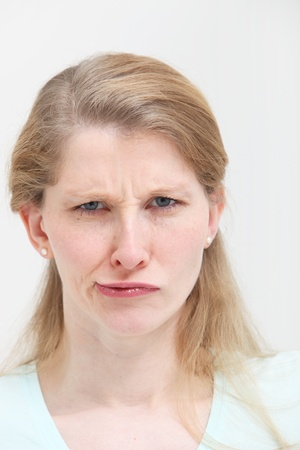 quizzical: Facial portrait of an attractive young blonde woman with a frowning lopsided quizzical expression