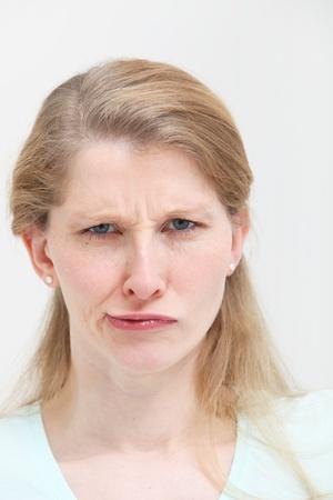 quizzical: Retrato de la cara de una atractiva joven rubia con una expresi�n frunciendo el ce�o torcido burlona