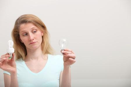 disdain: Mujer que sostiene una bombilla espiral ecol�gico luz en una mano tiene en la mira una bombilla incandescente de edad en la otra mano con desd�n