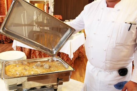 oven tray: Cropped view of a chef displaying a prepared meal in an oven tray reading for serving at the table in a catering concept Stock Photo
