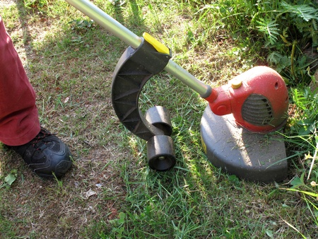 Person using a portable grass strimmer to cut the grass on rough overgrown terrain Stock Photo