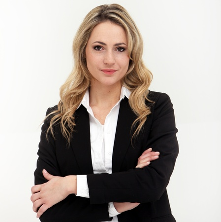 Studio shot of attractive business woman in black suit with arms crossed Stock Photo