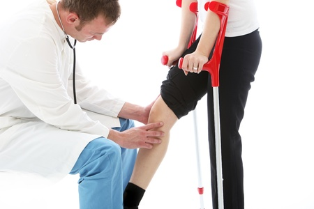 Orthopaedic surgeon sitting examining the knee of a female patient on crutches following surgery for a joint injury Stock Photo