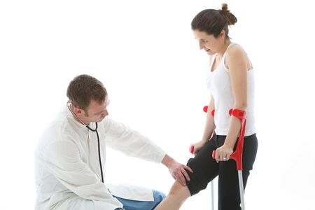 Orthopaedic surgeon examining the knee of a female patient on crutches during a post operative check-up