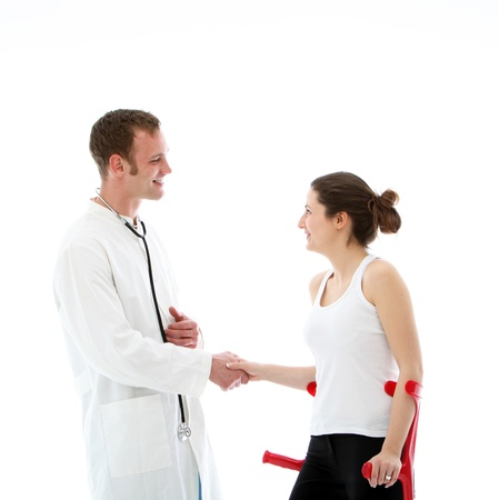 Smiling, kind doctor shaking hands with his female patient photo