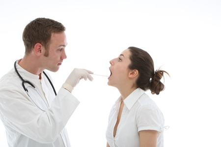 Young doctor examines throat of his patient on white background