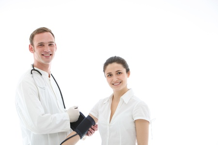 Smiling doctor applying blood pressure cuff to the upper arm of a female patient isolated on white Stock Photo - 13311882