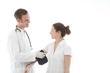 Smiling doctor applying the pressure cuff of a sphygmomanometer to take a blood pressure reading Stock Photo - 13311915