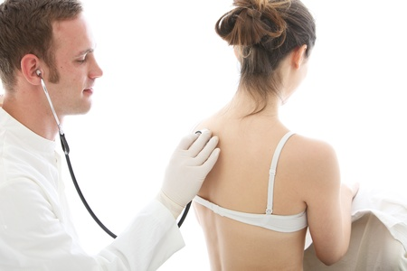 Doctor using a stethoscope to listen to a female patient breathing isolated on white