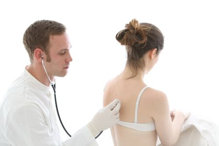 listening back: Doctor listening to the heart and lungs using a stethoscope on the back of a seated female patient wearing a bra