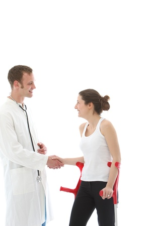 Grateful young disabled woman patient on crutches thanking her doctor by shaking his hand Stock Photo - 13311914