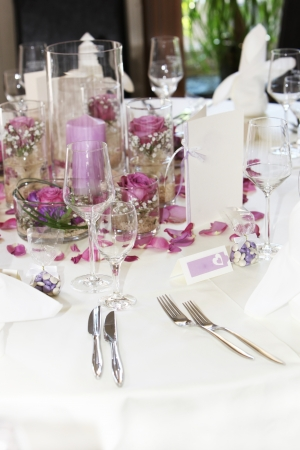 Beautiful floral table centrepiece with individual posies, scattered petals and candles on a wedding table photo