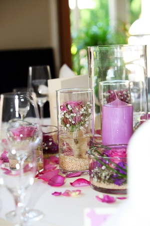 Delicate floral table centrepiece with individual small arrangements in glass containers, petals and a large candle on a wedding table photo