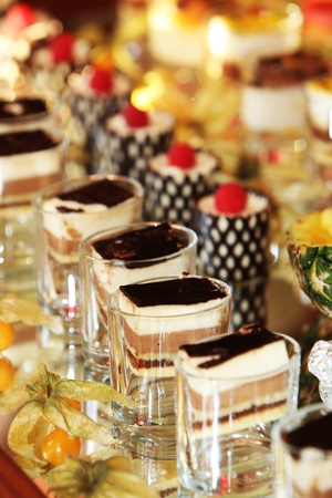 Beautifully served individual cakes and desserts on a buffet table at a luxury event Stock Photo