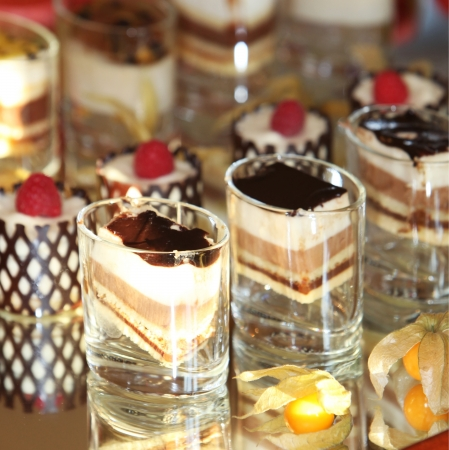 Selection of decorative gourmet desserts displayed on a mirror on a wedding buffet Stock Photo