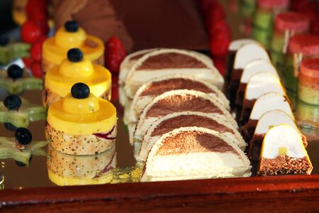 semicircular: Dessert tray with a choice of decorative individual little cakes and slices displayed on a buffet table
