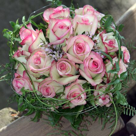 Beautiful bridal bouquet of perfect fresh pink roses entwined with delicate creeper