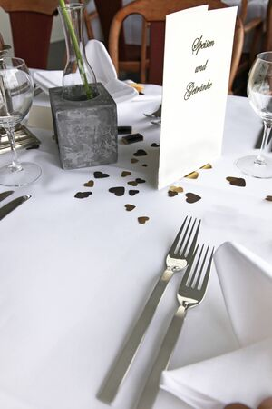 Decorative romantic table setting with scattered little golden hearts for a wedding , Valentines or anniversary photo