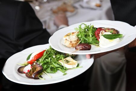 serving: Waiter carrying plates of starters with frsh rocket salad on the way to serve them to guests at a restaurant