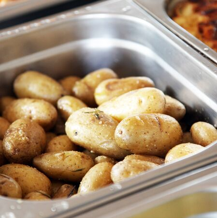 catered: Baked or boiled potatoes in metal dish on a buffet at a restaurant or catered event Stock Photo