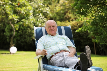 garden lawn: Retired man recling on a lounger and resting in the shade of a tree in his lush green garden with copyspace