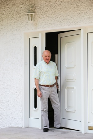 the elderly residence: Contented happy retired man standing in the doorway of his home with copyspace on white walls