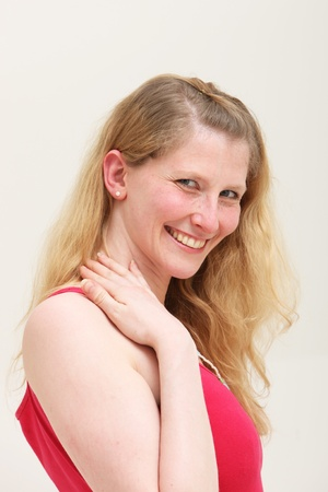 elated: Elated attractive middle-aged blonde woman smiling in pleasure as she looks down at the camera, studio portrait isolated on white Stock Photo