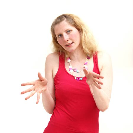 explanatory: Serious middle-aged woman facing the camera and explaining something with her hands which are extended in front of her with fingers spread Stock Photo
