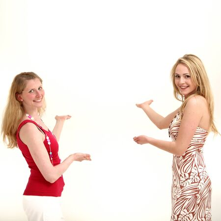 Two attractive friendly women standing facing each other with their palms out and other hands pointing to copyspace behind them as they coordinate a product placement concept